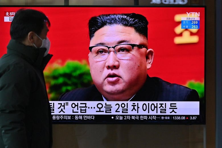 A man watches a television screen showing news footage of North Korean leader Kim Jong Un.