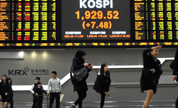 High school students walk past a stock index board as they visit the Korea Stock Exchange in Seoul.