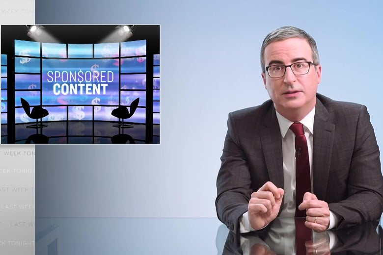 """John Oliver sits at his glass anchor desk in front of a chyron reading """"SPON$ORED CONTENT."""""""