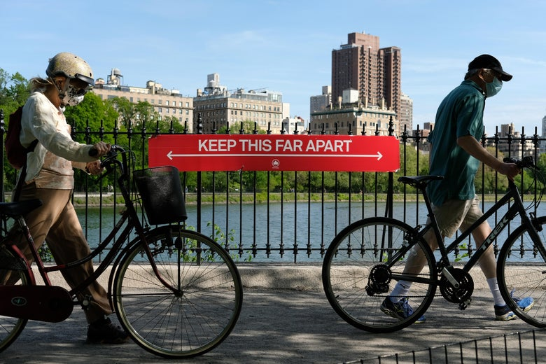 "People wearing protective masks walk their bicycles past a social distancing sign reading ""KEEP THIS FAR APART"" in Central Park."