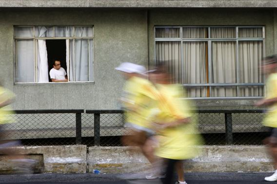 A resident looks out from a window of his apartment at people running during the Virada Esportiva program in Sao Paulo, July 1, 2012.