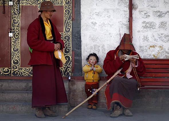 A Tibetan family rests outside Jokhang Monastery in Lhasa, Tibet, on March 4, 2014.