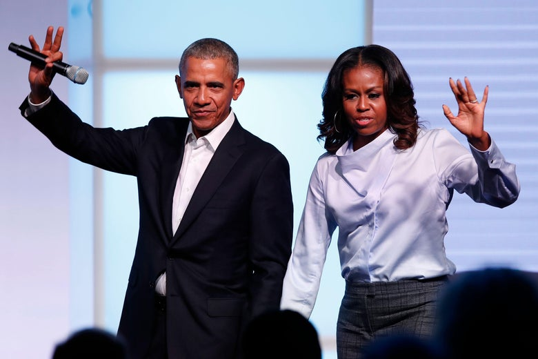 Barack and Michelle Obama hold hands on stage and wave out at the crowd.