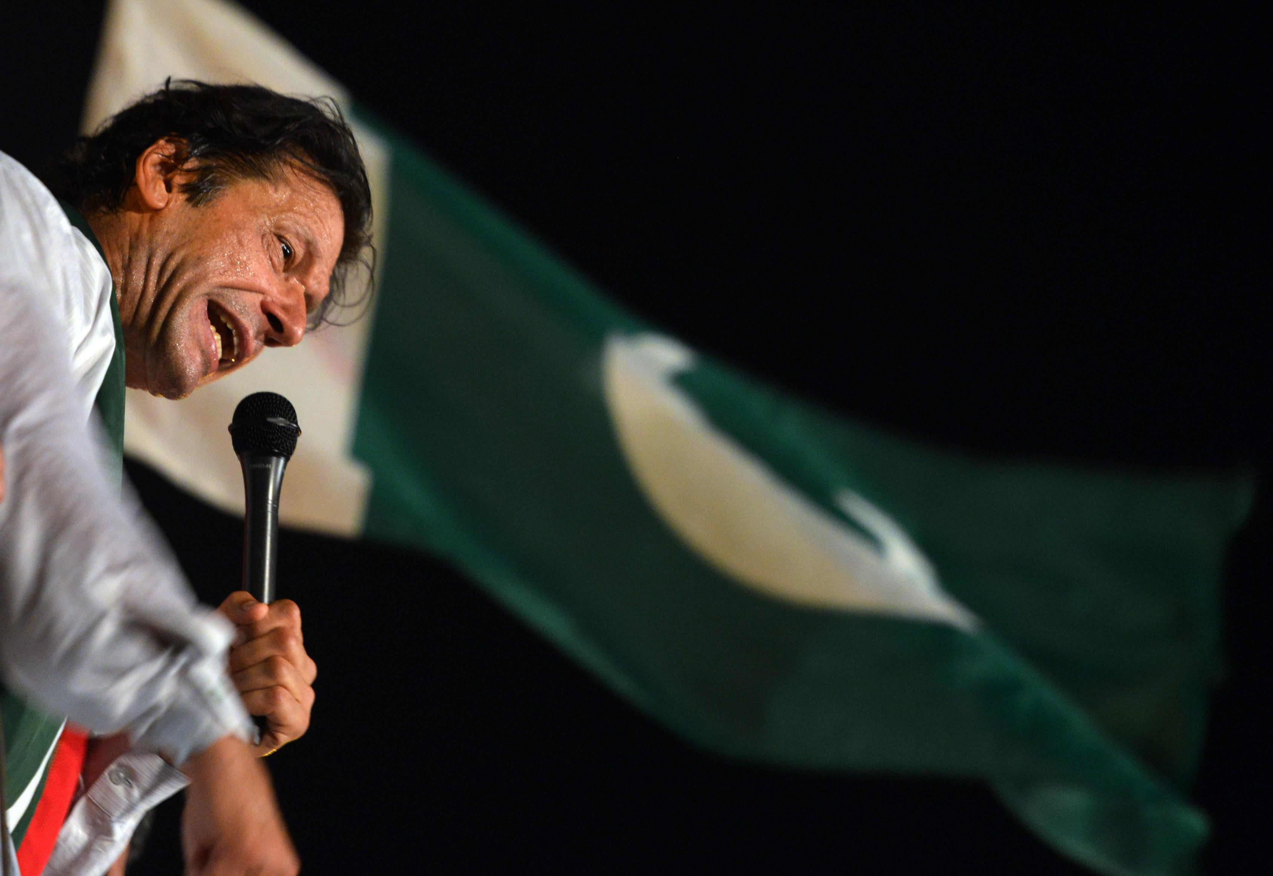 Pakistani opposition politician Imran Khan addresses his supporters during an anti-government protest in front of the Parliament building in Islamabad on August 21, 2014. Pakistani opposition politician Imran Khan on August 21, 2014 called off talks with the government aimed at ending protests seeking the fall of the prime minister, which have unnerved the nuclear-armed nation. Khan and populist cleric Tahir-ul-Qadri have led followers protesting outside parliament for the past two days demanding Prime Minister Nawaz Sharif quit.  AFP PHOTO/ AAMIR QURESHI        (Photo credit should read AAMIR QURESHI/AFP/Getty Images)