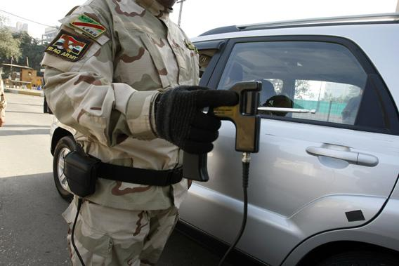 "An Iraqi soldier walk along side a car as he holds a ""bomb detecting device"" at a checkpoint in central Baghdad on Jan. 23, 2010."