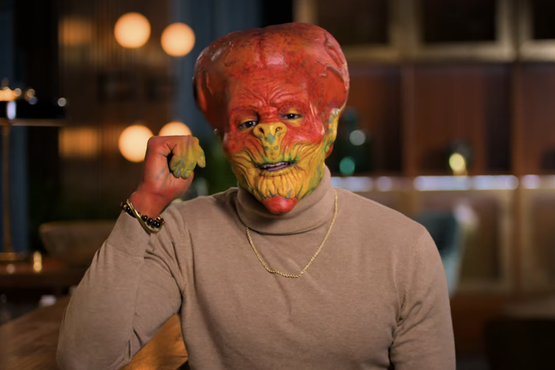Man in beige sweater wearing a red and yellow alien head.