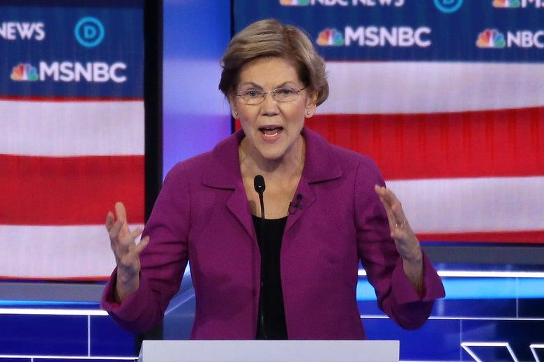 Elizabeth Warren raises her hands while speaking into a microphone.