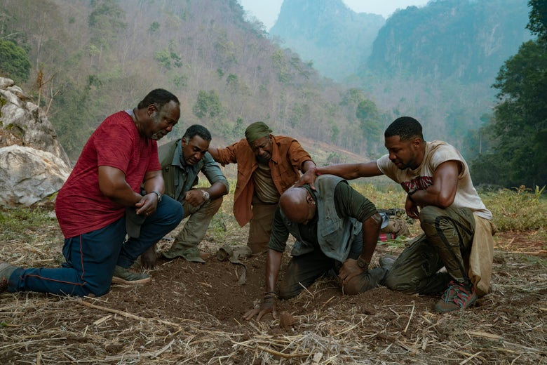 Still from Da 5 Bloods shows actors Delroy Lindo, Clarke Peters, Isiah Whitlock Jr., Norm Lewis, and Jonathan Majors kneeling solemnly around a hole in the ground.