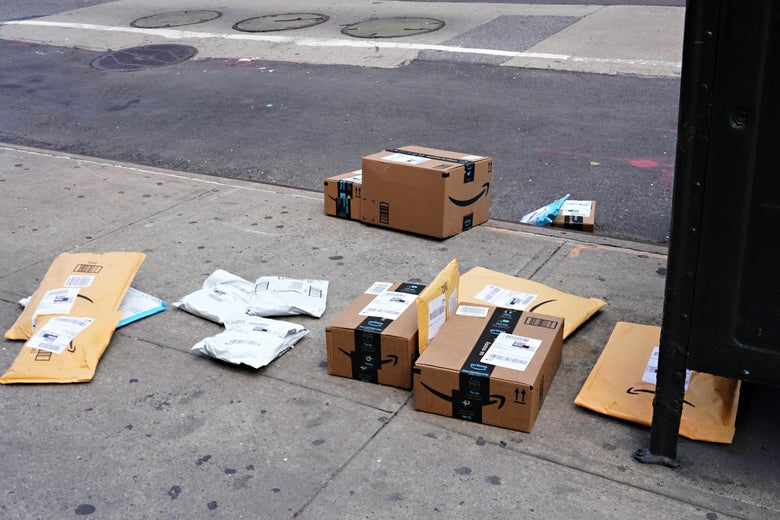 Amazon packages strewn across a city sidewalk.