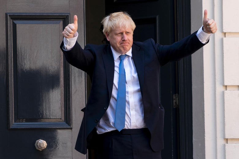 Boris Johnson standing outside a door with both arms raised in thumbs-up.