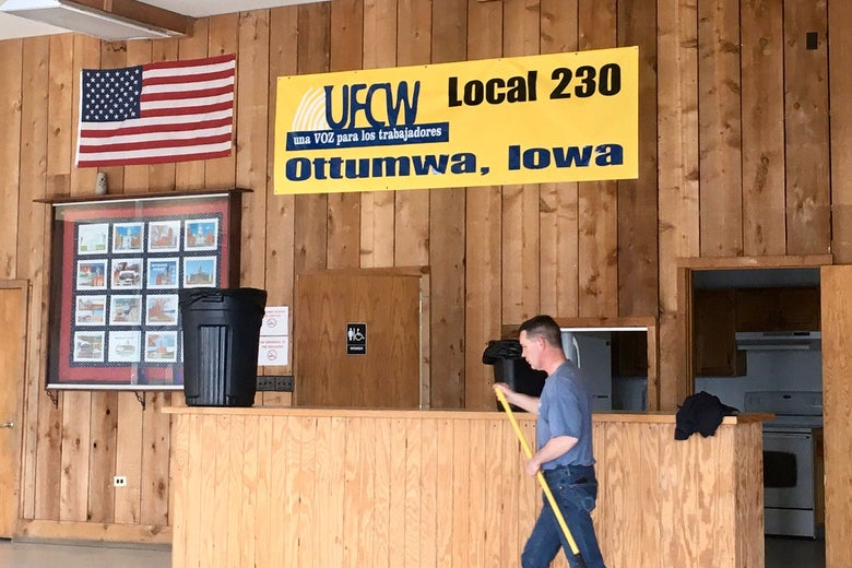 "A man sweeps or carries a broom in a union hall. A banner reads ""UFCW Local 230, Ottumwa, Iowa."""