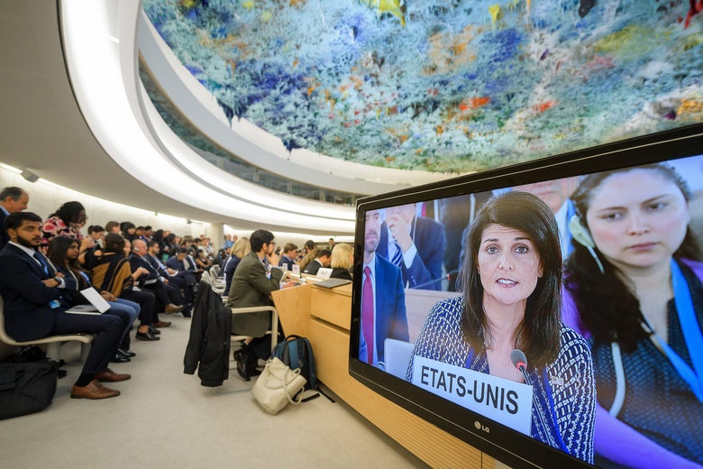 People sit next to a screening bearing a picture of US Ambassador to the United Nations Nikki Haley addressing a session of United Nations Human Rights Council on June 6, 2017 in Geneva.         The United Nations Human Rights Council opens a new session, with a speech from US envoy Nikki Haley following threats from Washington to quit the council over its treatment of Israel.                    / AFP PHOTO / Fabrice COFFRINI        (Photo credit should read FABRICE COFFRINI/AFP/Getty Images)