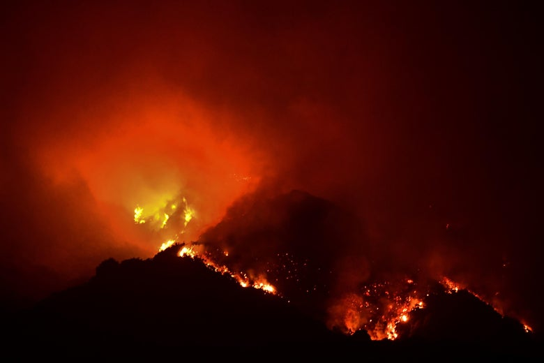 A wildfire rages over treetops, looking like an active volcano