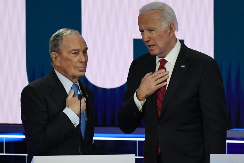 Bloomberg and Biden converse while holding their hands over the microphones that are affixed to their suits.