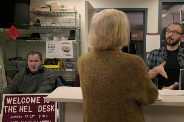 Joan standing at an IT desk talking to two men.