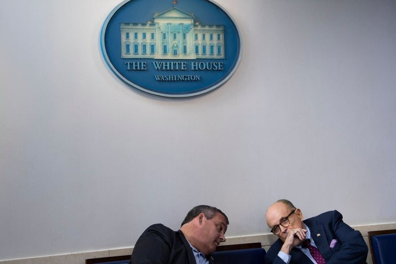 Christie and Giuliani confer while seated on a couch under a White House seal.