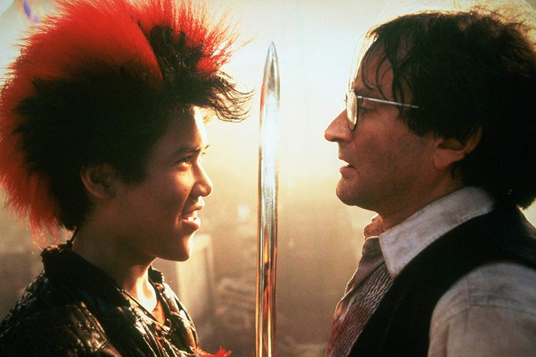 Dante Basco, with a red-tipped mohawk, holds a sword up to a bespectacled Robin Williams.
