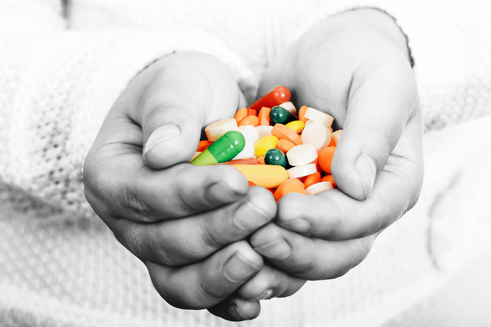 A child's hands cupping a colorful assortment of prescription pills.