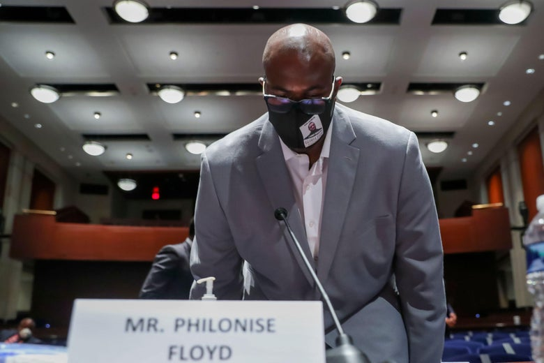 Philonise Floyd, wearing a mask, taking a seat with his name plate.