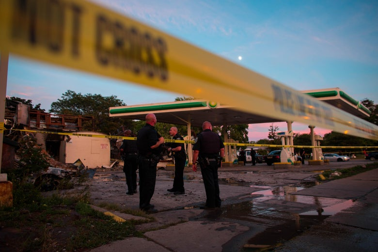 Police officers stand guard as crowds gather for a second night near the BP gas station that was burned after an officer-involved killing August 14, 2016 in Milwaukee, Wisconsin.