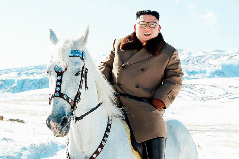 Kim grinning, astride a white horse, with snow-capped mountains in the background.