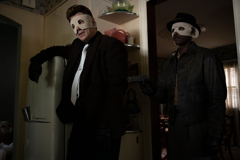 The two actors wear crude white masks and 1950s clothes in a 1950s kitchen