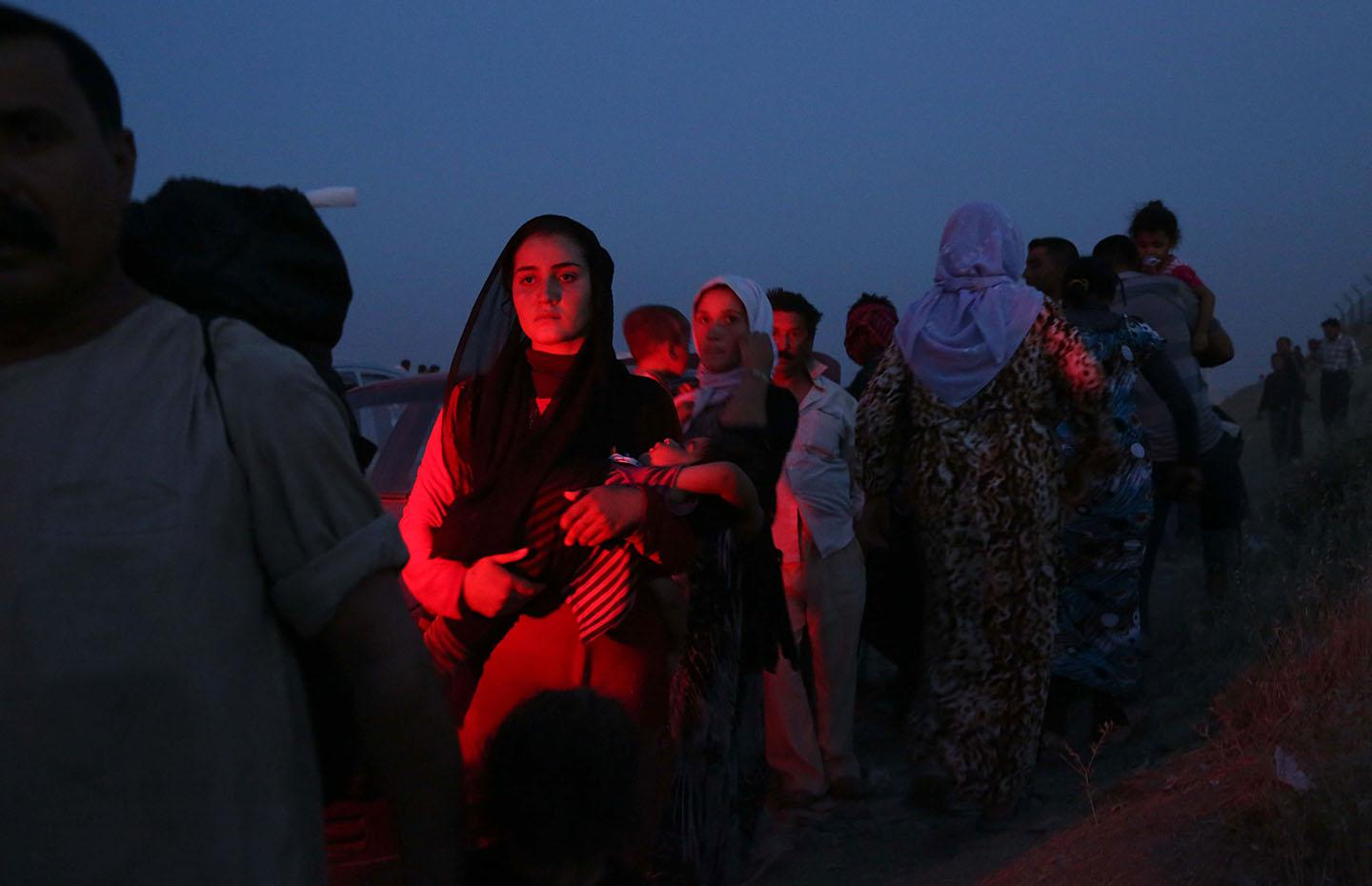 Thousands of Iraqis flee from Sinjar, near the city of Mosul, to Erbil and Dohuk, after armed ISIS groups seized the town early on August 4, 2014.