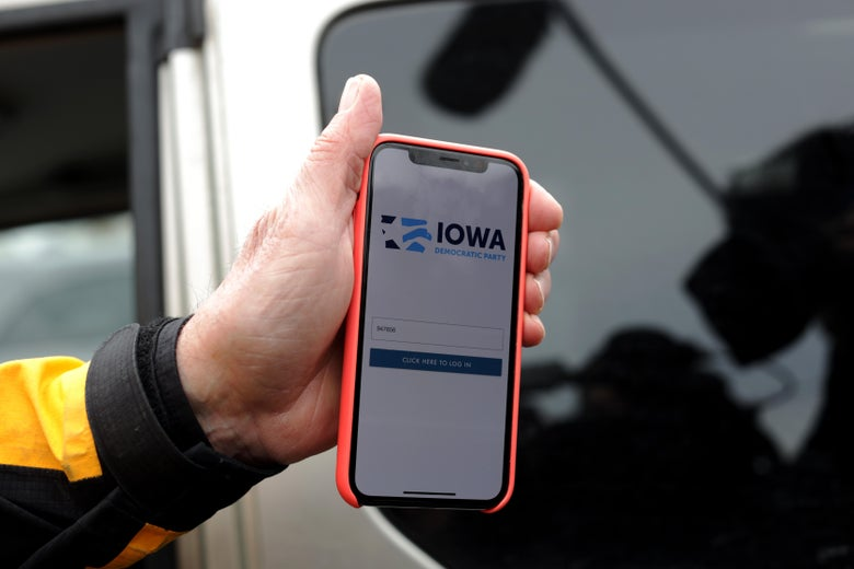 A hand holds a smartphone showing the sign-in interface for the Iowa vote reporting app.