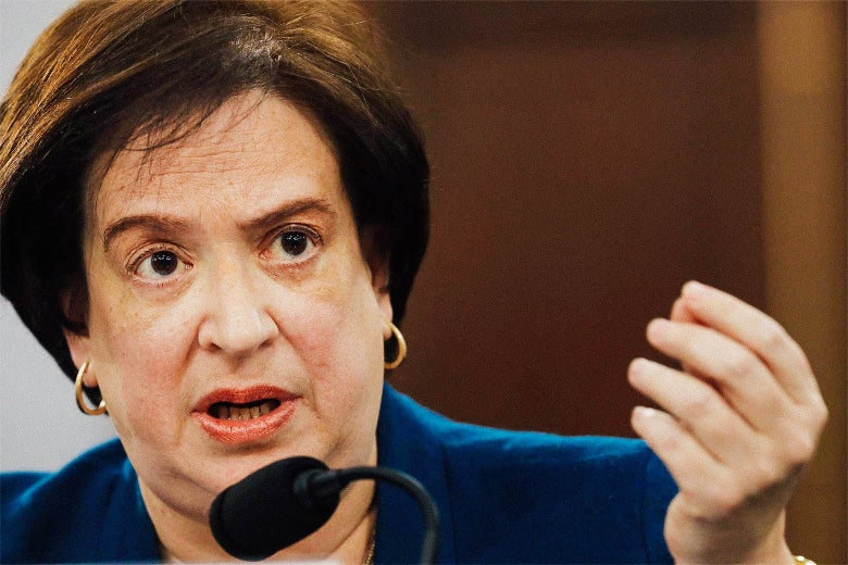Elena Kagan speaks into a microphone and raises her hand.
