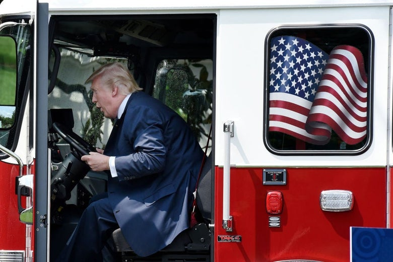Trump leans forward in the cab while apparently making some sort of noise with his mouth.