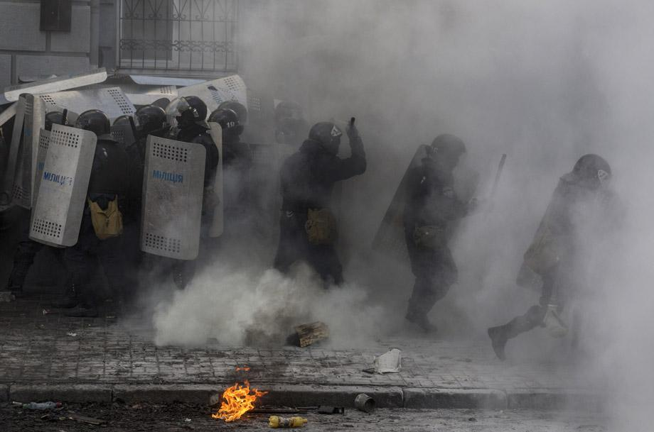 Government police take cover behind shields during clashes with protesters in Kiev on Feb. 18, 2014.