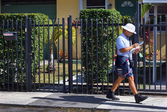 A mailman for the U.S. Postal Service delivers mail on Nov. 15, 2012, in Miami.