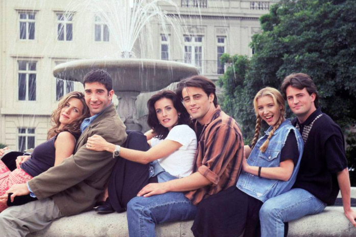 The Friends cast sits on a water fountain.