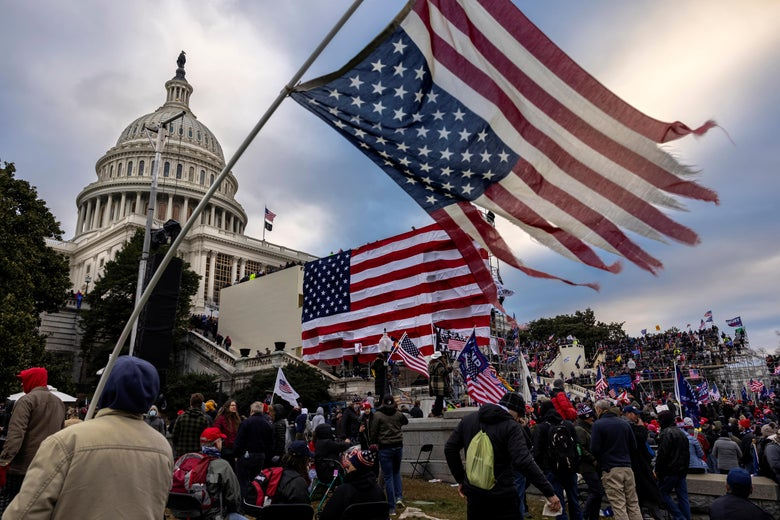 A frayed upside-down American flag flies in front of Trump supporters massed on the Capitol steps.