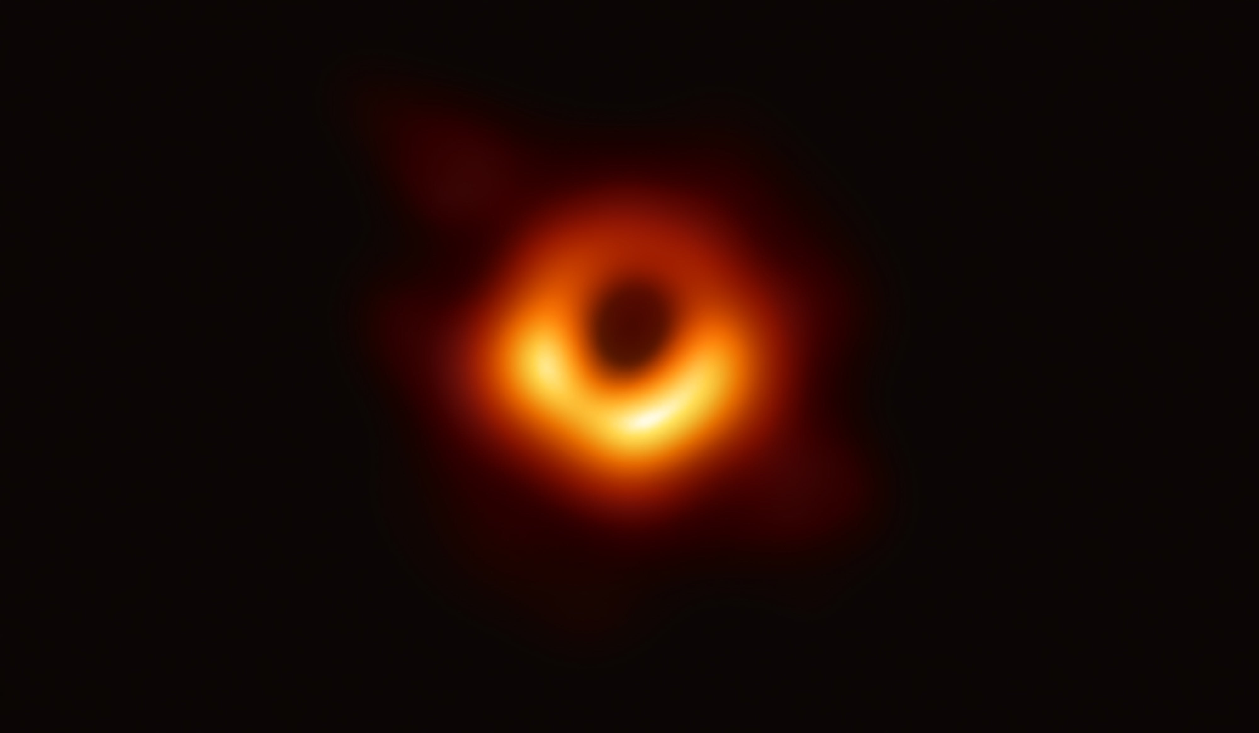 The photo of the black hole. It appears as a blurry ring of red and yellow light, dimmer on one side, with a flare of light radiating from that ring.
