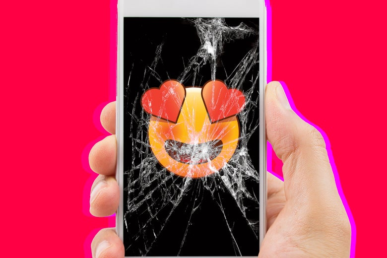 Photo illustration: A heart-eyes emoji is shown on the screen of a severely cracked phone in someone's hand.
