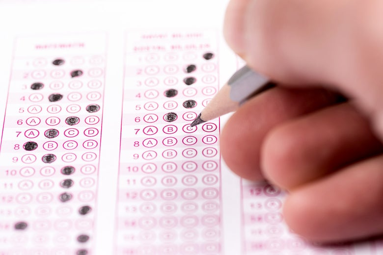 A hand holding a pencil over a multiple choice test form on which some bubbles have already been filled in.
