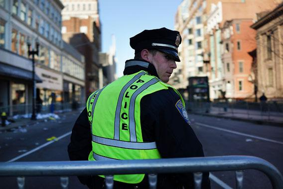 A Boston police officer stands near the scene of a twin bombing at the Boston Marathon on April 16, 2013 in Boston, Massachusetts.