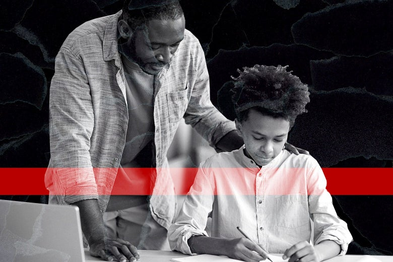 A man looks over his son's shoulder as he does homework.