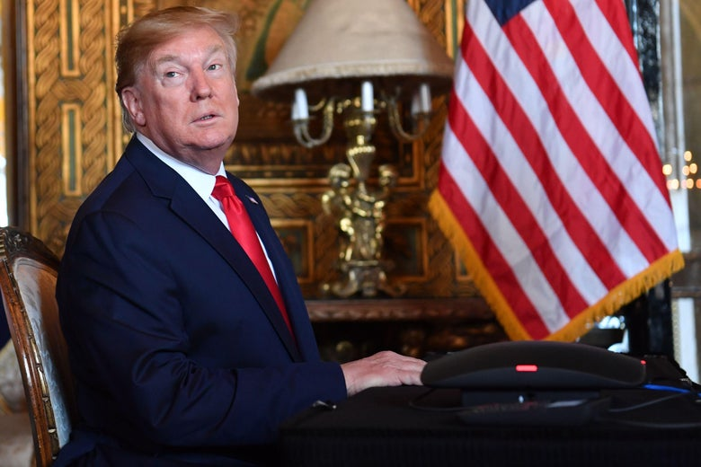 Donald Trump turns toward the camera while seated at a desk in an ornate office.
