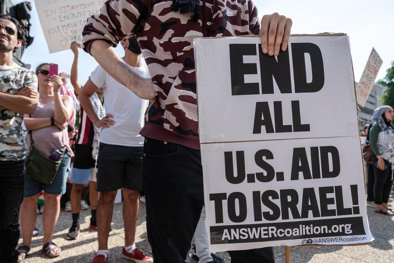 """A man holds a sign that says, """"End all U.S. aid to Israel."""""""
