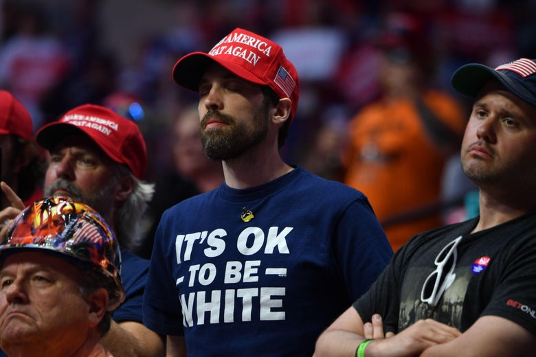 "Man wearing an ""It's OK to Be White"" shirt in the audience of Trump supporters listening as Trump speaks"