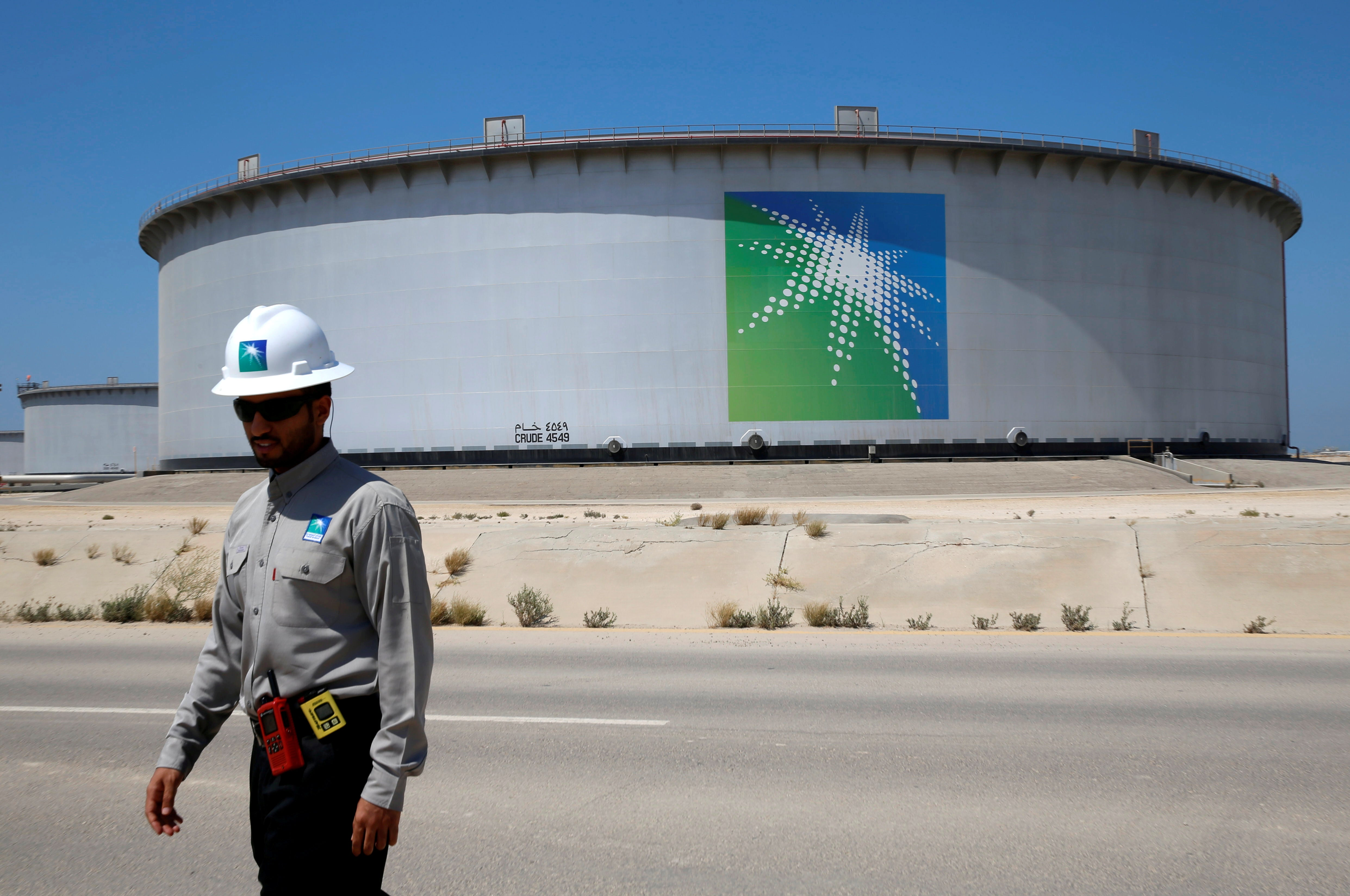 A ban in front of an oil tank with the Aramco logo on it.