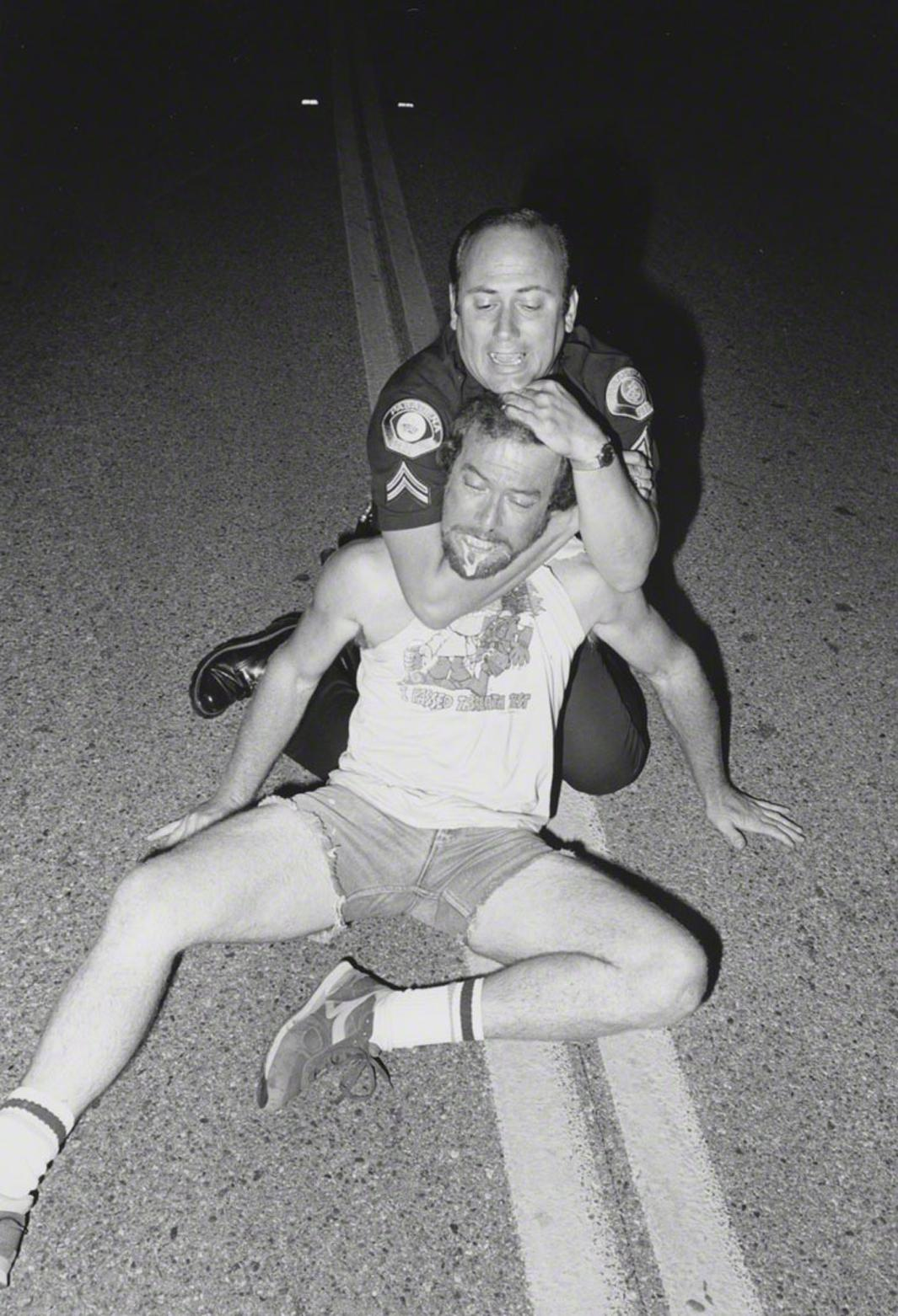 "6/7/86 Agent Baroni applying carotid hold to suspect under the influence of PCP who attacked our police car. (note that the suspect's T-shirt says ""I passed the Breath Test""). Melrose Avenue and Avenue 64."