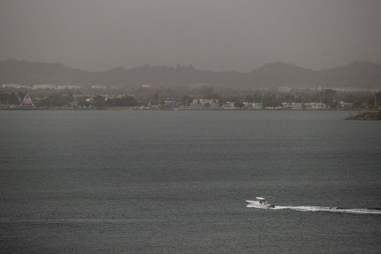 A boat speeds across a bay in front of a shoreline enveloped in a haze. The air is gray, and the mountains and buildings are barely visible.