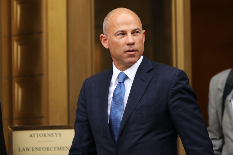 Michael Avenatti walks outside in front of gold-framed doors.