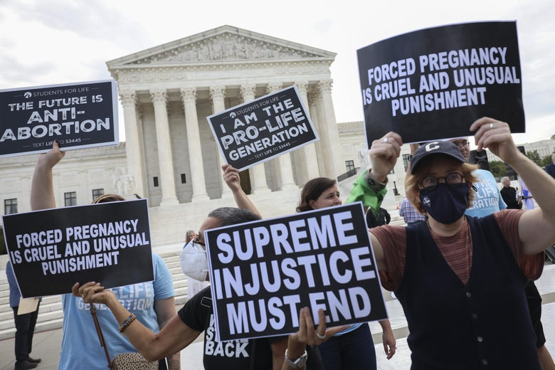 People hold signs with pro-choice and pro-life slogans in front of the Supreme Court building.