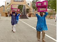 Indian porters carrying goods to the border of Pakistan at Wagah