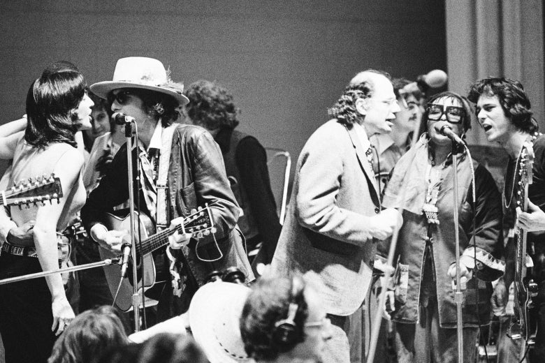 Baez and Dylan sing into one mic as Ginsberg and Flack sing into another during a performance