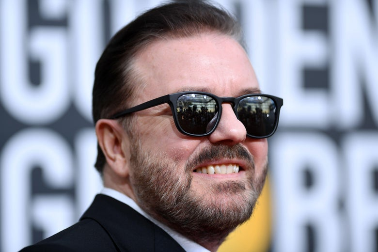 Ricky Gervais smiling in sunglasses with a shit-eating grin.